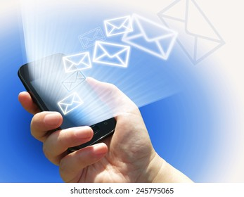 electronic communication - sending e-mails from mobile phone - hand holding a phone