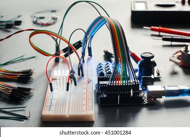 Electronic component connected with breadboard in laboratory. Electrical engineering with led and microcontroller on programmer workplace. Hacker conduct experiment with computer technologies