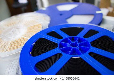 Electronic components, capacitors in tape, in blue and white coils. Capacitors in tape and reel. Photography of capacitors in tape, in blue and white coils. Blue, black and white background.
