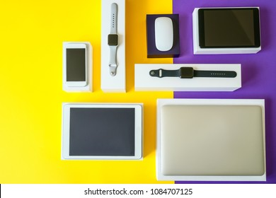 Electronic devices- computer, tablet, computer mouse, disc drive, smartphone and smart watch . Technology mock up. Colorful background, top view.