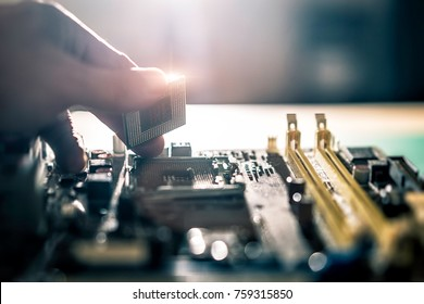 Electronic engineer of computer technology. Maintenance computer cpu hardware upgrade of motherboard putting the CPU on the socket of the computer motherboard.
