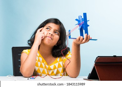 electronic experiment - Asian Indian small girl student performing windmill research with wires, connections, studying from laptop or tablet computer