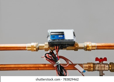Electronic heat meter on copper pipes with valve. Grey background with space for text.