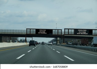 Electronic information sign over a busy multi-lane highway that says Coronavirus stay home to stop the spread