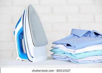 Electronic ironing and pile of clothes on board on brick wall background