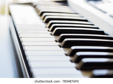 An electronic keyboard is in a bright room placed next to an open window. This is a bright image with the focus being on the keyboards ivory keys.