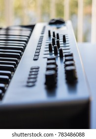 An electronic keyboard is set in a bright room. It has an 8 channel control board built in with faders and knobs.
