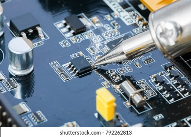 Electronic manufacturing and repair concept - close up studio shot of soldering iron and microcircuit next to it