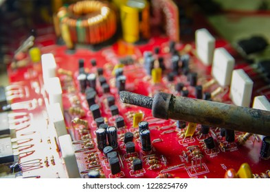 Electronic manufacturing and repair concept - soldering iron and microcircuit next to it - close up studio shot