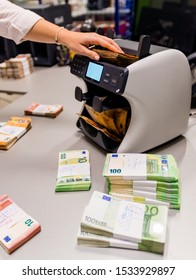 Electronic money counter with € euro bills, female office worker counting money Euro banknote of treasury department for cash machine refill