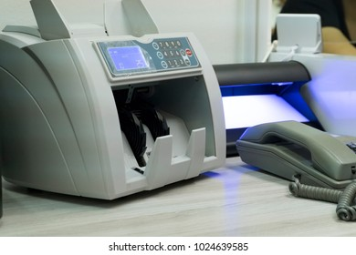 electronic money counter machine and fake detector on cashier table