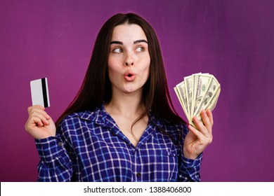 Electronic money vs cash. Young pensive woman with credit card and dollar bills. Online payment, savings, financial concept