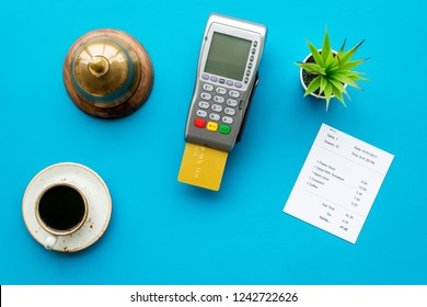Electronic payments. Pay the bill by card concept. Bank card inserted in payment terminal near bill, service bell, coffee on blue background top view