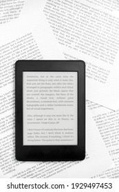 Electronic reader with the screen on and a text on it, on sheets of paper with text printed on them. Concepts: reading and digital technology. Flat lay image with copy space.