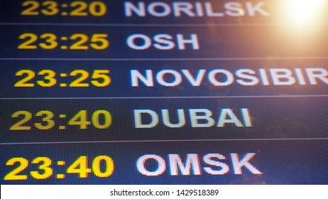Electronic scoreboard flights and airlines. Destinations: Norilsk, Osh, Novosibirsk, Dubai, Omsk. Airport flight information arrival displayed on departure board, flight status changing