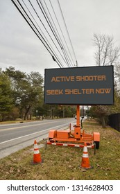 Electronic sign near a road that says, Active Shooter Take Cover Now. There is a blue sky and cars on the highway