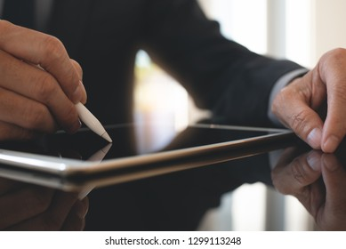 Electronic signature, Business and modern technology concept. Businessman using digital tablet signing electronic document with digital pen on mirror desk with reflection in modern office, close up