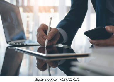 Electronic signature, Business technology concept. Businessman working on digital tablet signing contract with digital pen, holding mobile phone, laptop computer and business document on office desk