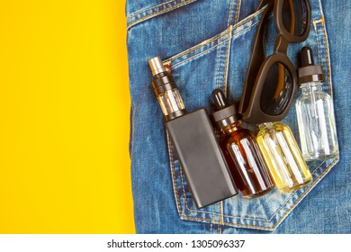 Electronic smoking kit. Vape pen with  bottles of liquid for refilling electronic cigarettes. Modern accessories for vaping.