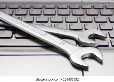 electronic technical support concept - spanners on computer keyboard