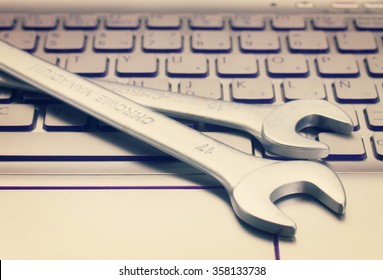 electronic technical support concept - spanners on computer keyboard, retro toned