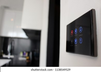Electronic touch screen light and temperature control panel wall mounted in a modern apartment room.