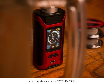 Electronic vaping mod on a wooden table - view through the glass holder of the glass. In the background, a coils of wire for forming heating coils.