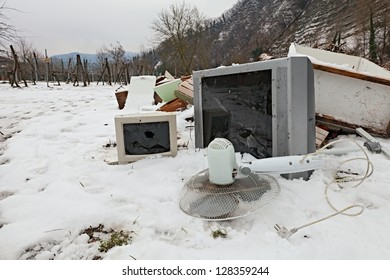 electronic waste and electrical appliance abandoned in the snow -  illegal waste dump in the countryside