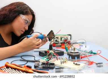 Electronic workshop, young lady soldering components of an Arduino project