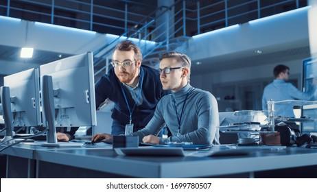 El ingeniero de desarrollo de electrónica usa charlas personales con el gerente, muestra el proyecto. Equipo de Profesionales utiliza pizarra electrónica digital con software CAD para el diseño moderno de ingeniería industrial
