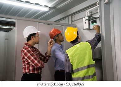Electronics engineer or contractor, vest and safety helmet, checking electronic control box. Real estate, industrial supply background concept. Vocation workshop.