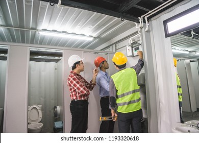 Electronics engineer or contractor, vest and safety helmet, checking electronic control box of toilet. Real estate, industrial supply background concept. Vocation workshop.