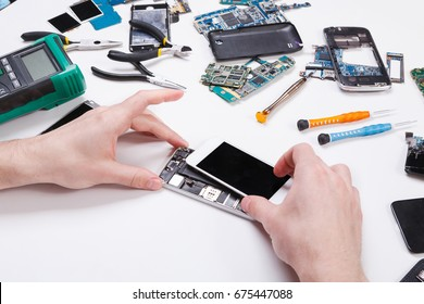 Electronics repair service. Repairman disassembling smartphone for inspecting. Technician fixing broken phone, copy space for text