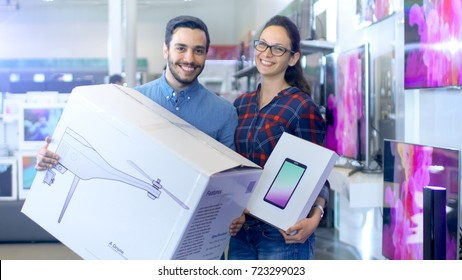 In the Electronics Store Happy Young Couple Poses with Newly Purchased Drone and Tablet Computer. Store is Big and Bright, Has All the Latest TV's, Cameras and Smartphones.