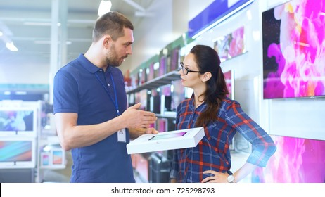 In the Electronics Store Professional Consultant Provides Expert Advice on Tablet Computer Specifications For Beautiful Young Woman. Store is Bright, Modern and Has all the Latest Devices.