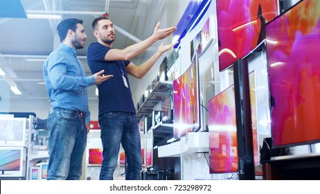In the Electronics Store Professional Consultant Shows TV's to a Young Man, They Talk about Specifications and What Model is Best for His Home. Store is Bright, Modern and Has all the Latest Models.