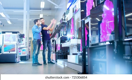 In the Electronics Store Professional Consultant Shows Latest 4K UHD TV's to a Young Man, They Talk about Specifications and What Model is Best for Young Man's Home. Store is Bright.