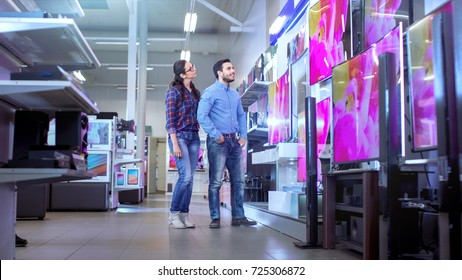 In the Electronics Store Young Couple is Choosing Which a New Model of 4K TV's is Best for Their Home and Budget.