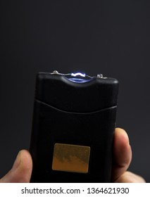 Electroshock Taser in the hand of a man on a black background.