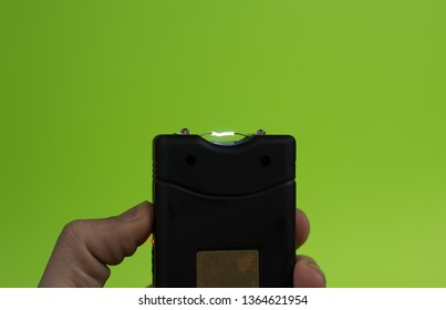 Electroshock Taser in the hand of a man on a green background.