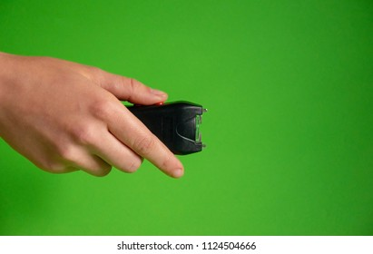 Electroshock Taser in the hand of a woman on a green background, Methods of self defense, danger