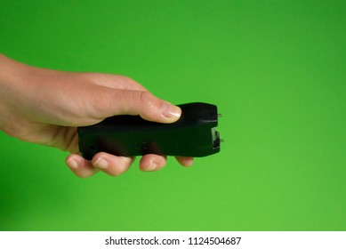Electroshock Taser in the hand of a woman on a green background, Methods of self-defense, danger