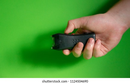 Electroshocker in the hand of a man on a green background, Methods of self-defense, danger