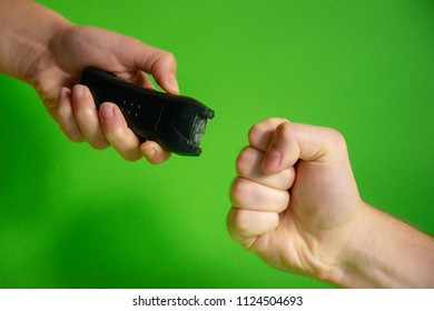 Electroshocker in the hand of a woman and the fist of the intruder on a green background, Methods of self defense, danger