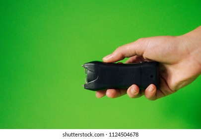 Electroshocker in the hand of a woman on a green background, Methods of self defense, danger