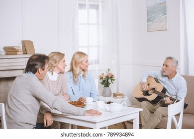 eleder man playing guitar while another people sitting at table