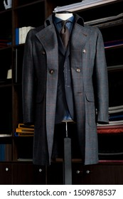 Elegance bespoke winter-coat with suit, brown tie and navy blue shirt on a mannequin. Men's Clothing.