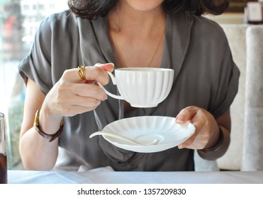 Elegance female holding white cup and plate in English etiquette, crop not have face beautiful woman sitting relax with high tea time at restaurant, for happy with afternoon tea concept