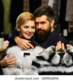 Elegance and glamour concept. Couple in love tries expensive sable overcoats on. Guy with beard and woman buy furry coat. Man and girl with happy faces hold furry coats on clothes rack background.