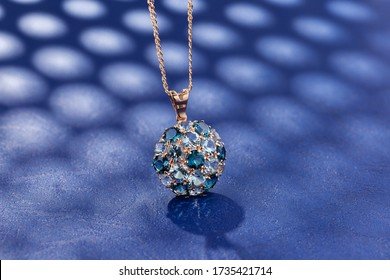Elegance gold pendant necklace with blue topaz gemstones on blue background. Fashion jewelry with natural gemstone